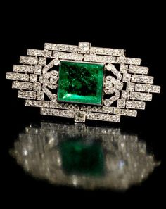 *An art deco emerald and diamond brooch, circa 1925 The central step-cut emerald, between highly stylised anthemion motif shoulders, within a pierced crenellated border, millegrain-set throughout with old brilliant and single-cut diamonds, mounted in platinum, emerald approximately 9.30 carats, diamonds approximately 3.50 carats total, partial maker's mark, French assay marks, diameter 6.5cm