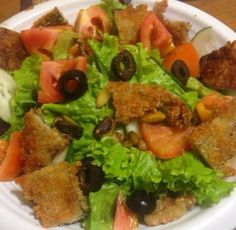 Salad made with green lollo rosso, olives, tomatoes and eggplant croutons