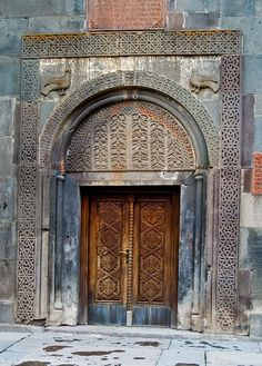 Intricate lace carvings in wood and stone. A door at the Geghard Monastery in Armenia.