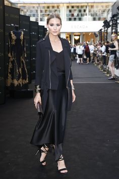 Olivia Palermo in a silk wrap skirt, dainty tank, thin moto jacket, wide studded belt, chunky bracelets, a sequined clutch and tasseled heels.
