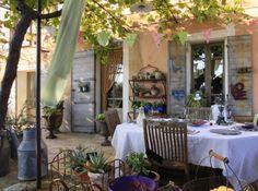 L'Atelier de Betty : terrasse couverte d'une pergola dont le feuillage dessine une zone ombragée et délimite un coin repas, esprit brocante & romantique. Sur les traverses en arc de cercle, de jolis fanions en tissu rose et vert se mêlent aux vrilles de la vigne vierge. Sur les volets en bois : des décorations en ardoise soulignent la douceur de la patine gris-bleu. Sur l'étagère en fer forgé : des pots en terre cuite accueillent des plantes grasses.