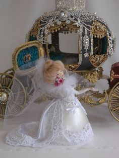 A bride preparing to toss her bouquet just before entering her royal carriage.  Bride is made by me using a rhea egg shell, appliques and lace, with bisque face and arms.  Hair is alpaca.