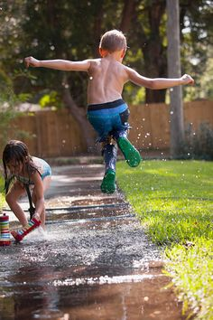 Boy in wellies jumping in mid-air on sidewalk