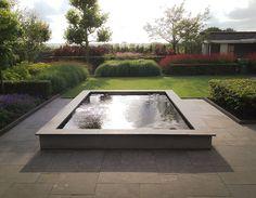Moderne grote tuin met strakke verhoogde vijver en weelderige beplanting.