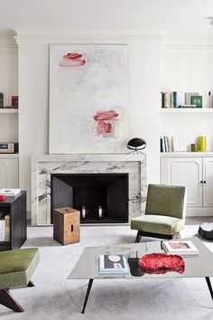 Marble fireplace, modern art, and green chairs in a Paris apartment.