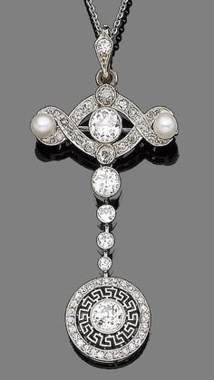 A pearl and diamond brooch/pendant necklace, circa 1910  The scrolling openwork plaque set with two pearls, cushion-shaped and old brilliant-cut diamonds, suspending a row of graduated collet-set old brilliant-cut diamonds, terminating in a similarly-cut diamond within a pierced Greek key motif border and a further single-cut diamond surround, millegrain-set throughout, to a fine trace-link chain, diamonds approx. 2.30cts total