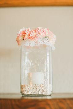 Romantic Garden Wedding Idea: Square mason jar lined with white rocks and a candle. Top it off with a wreath of flowers.