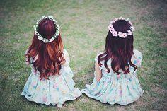 お揃いの花かんむりで満足げな双子の女の子たち