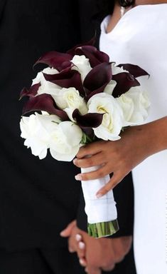 Wedding bouquet of dark burgundy calla lilies with white roses, hand tied with ribbon.