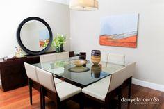 Sala de jantar com mesa quadrada com tampo de vidro para oito lugares, quadro colorido, espelho redondo, iluminação pendente, buffet em madeira, piso de madeira. Sala decorada, decoração. Repaginada na decoração sala de estar e jantar do apto