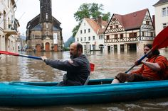 Two men in a boat cross the flooded marketplace of Wehlen, Germany at the river Elbe on June 4, 2013. (Markus Schreiber/Associated Press) #