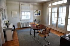 Dining room with light wood floors, gray area rug.