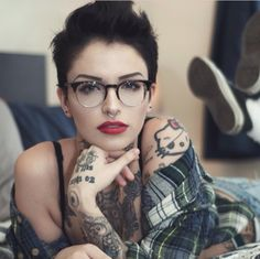 Pixie cut, septum piercing, horned glasses, tatoos, classic makeup, and plaid.