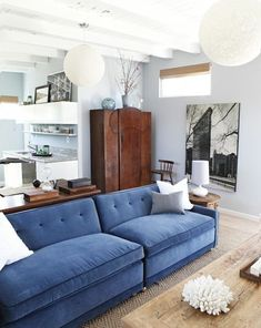 This stunning living room design by Emily Henderson gets a jolt of color from a pretty blue sofa. Store your things in a wood armoire and on top of a sofa table. My Living Room, Home And Living, Living Room Decor, Living Spaces, Blue Velvet Couch, Blue Couches, Navy Couch, Velvet Color, Casa Milano