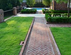 FENCE This herringbone brick path with raised brick border creates a perfect axis to the swimming pool. The courtyard is enclosed by brick columns with custom wrought iron fencing and accented with an elegant boxwood hedge and zoysia sod. Brick Columns, Brick Pathway, Front Walkway, Brick Paver Driveway, Wood Walkway, Brick Steps, Flagstone Patio, Brick Fence, Front Steps