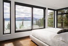 modern lake house in Canada has an exterior clad in wood, stone, and metal This master bedroom has black window frames that contrast the white walls, and a door leads to a private balcony with amazing lake and mountain views. Master Bedroom Bathroom, Modern Master Bedroom, Large Bedroom, Home Bedroom, Master Bedrooms, Bedroom Ideas, Trendy Bedroom, Bath Room, Modern Windows