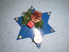 Stern aus dünnen Sperrholz aussägen und beliebig streichen, in eine Ecke Laternenteelichthülle mit Reiszwecke befestigen, Weihnachtsschmuck ankleben
