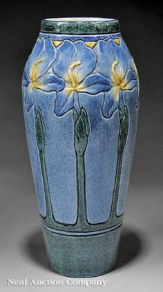 "A Fine Newcomb College Art Pottery High Glaze Vase, 1908, decorated by Leona Fischer Nicholson with a relief-carved design of orchid tree blossoms, base with Newcomb cipher, decorator's mark, Joseph Meyer's potter's mark, ""W"" for white clay body, and reg. no. CE2, height 12 1/2 in., diameter 5 1/2 in"