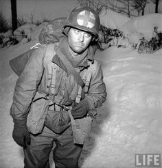 Tired American medic returning from the front lines during the Battle of the Bulge.