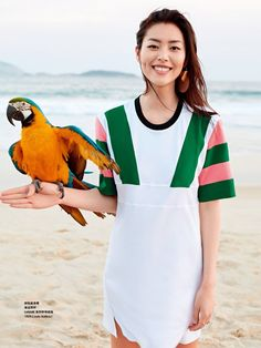 Liu Wen is all smiles as she poses with a parrot for Grazia China Magazine June 2016
