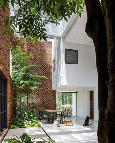 Walls of punctured bricks create an intriguing pattern and let breezes waft through the courtyard of this multi-generational house in Bien Hoa. Luz Natural, Natural Light, Concrete Cover, Outdoor Spaces, Outdoor Living, Outdoor Lounge, Square Windows, Vietnam, Two Storey House