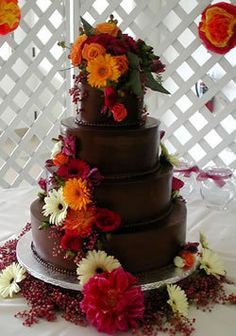"The chocolate brown icing on this four-tier, round wedding cake really makes the autumn toned gerbera daisies, dahlias, and other flowers ""pop""."