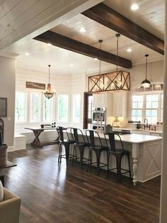 I love the rustic feel of this kitchen. how the floors accent the wood beams along with the dark light fixtures that match the chairs.