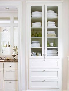 Investigate space between the bathroom wall studs, and you might discover hidden storage. Even if the space between rooms is shallow, shelves built floor-to-ceiling between studs can hold a large amount of supplies and toiletries. If desired, add doors to conceal the clutter. Glass-front cabinets help the bathroom feel open and airy./