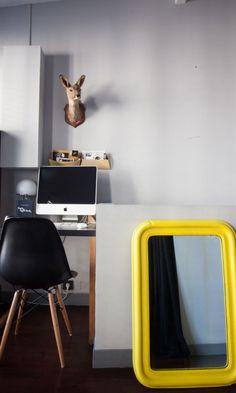Coin bureau, chaise Eames et trophée biche au mur, posé à coté un miroir repeint en jaune. - The Socialite Family