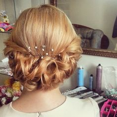 low curly roll updo for medium length Here is a beautiful bridal look. This style combines a gorgeous roll of curls with a delicate hair accessory. The pearls are just large enough to catch the eye, but small enough to allow the style to be the focal point; a lovely look for ladies with medium to long hair lengths.