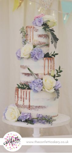 Modern semi-naked wedding cake. With blue and white buttercream and rose gold drips. Fresh rose, hydrangea, lisianthus delphinium and Veronica decoration. Cake & Image: The Confetti Cakery. Venue: East Bridgford Hill.