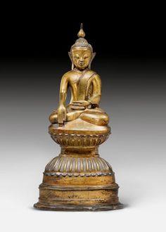 BUDDHA AUF HOHEM SOCKEL. Burma, Ava, 16. Jh. H 42,5 cm Bronze. Shakyamuni sitzt auf einem mehrfach getreppten Lotossockel mit eingezogener Taille. Er sitzt in Maravijaya-Pose und trägt ein einfaches Mönchsgewand. Ein Lächen erhellt das jugendliche Gesicht mit den markant schräg gestellten Augen und Augenbrauen.