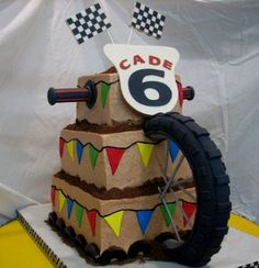 Dirt Bikes - This is a cake done for two little boys with a dirt bike themed party. The cake is actually two sided. Each side is identical with the exception of the boys names.  The wheels are foam hoops coverd with gumpaste.  The spokes are skewers covered with gumpaste.  The handle bar grips are done with gumpast around a large dowel.  The flags and number plaques are all gumpaste as well.  The cake is done in buttercream with fondant accents.  The dirt is ground up chocolate graham…