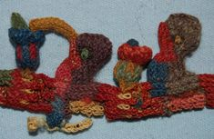 Textile fragment; camelid fibre; cross knit loop stitch; row of humming bird motifs with long beaks dipping into plants; alternate with larger plant motifs; reds, pinks, indigo, green and browns. Nazca, 100BC-600.  Registration number: Am2006,Q.20