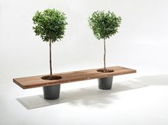 Romeo & Juliet is no ordinary bench. It not only offers passers-by a comfortable place to sit and relax, but it also adds a touch of green to the environment. The bench is made of long square strips of wood. Two round holes in the seat create room for large flowerpots containing a small tree. The bench seems to literally float between the pots.