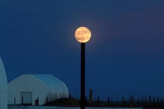 The supermoon appears to rest on top of a pole in this photo by Gandhi Kumar in Boulder, Colorado.