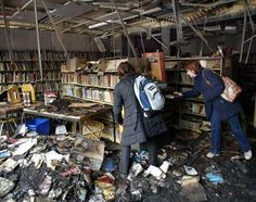 Reporters and school workers inspect the damage at the United Talmud Torah elementary school in Montreal on April 5, 2004, after the school's library was firebombed overnight.