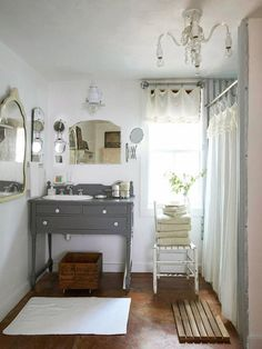Vintage bathroom! Lot of mirrors in different shapes, grey white and warm wood colours, sink submerged into an old dresser, beautiful natural light, clean fluffy towels.... I love every little bit of this bathroom!