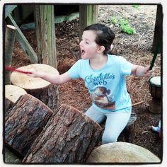 I child enjoying the log drum set in the Childrens Garden at Lewis Ginter Botanical Garden. Photo by chuckmalcomson