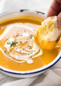 Close up of dunking crusty bread into thick and creamy pumpkin soup in a rustic white enamel bowl.