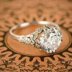 A stunning Edwardian style era engagement ring centering a 3.56ct old European cut, L color, VS1 clarity diamond. Along the shoulders and the gallery of the ring is a bow motif which sets the diamond. The bow motifs are adorned with diamonds. This ring is entirely hand-crafted in