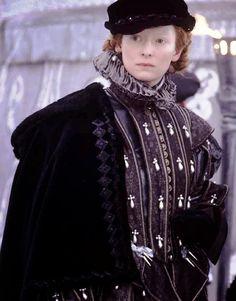 ilda Swinton vestida a la moda española del siglo XVI, con gorra de copa baja de terciopelo,cuello de lechuguilla, doublet ornado con perlas y bohemio de terciopelo forrado de piel