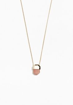 An elegant brass necklace featuring an angular stone pendant. Due to the nature of the stone, each piece has a unique appearance.