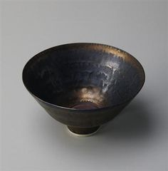 Lucie Rie, Footed bowl, Porcelain, bright golden glaze, a terracotta disc in the well. 7 1/4 in. (18.4 cm.) diameter, c.1974