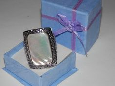 This is a WOW ring that is beautiful ! Has the iridescence of a beautiful pearl and the design on the mounting makes this very upscale! Measures 1 1/8th of an inch long and a little over .75 of an inch wide. 18k white gold plated. Will ship in an adorable box. Size 6