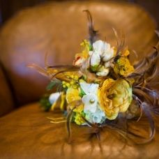 Lovely feather adorned  bouquet in yellow.