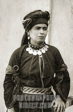 raq Kurdish woman in her best costume of black Persian silk with silver belt and her necklace of amber beads with Turkish coins attached