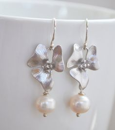 "❘❘❙❙❚❚ ON SALE ❚❚❙❙❘❘ Order will be shipped on/after March 29, 2017     Super SWEET handmade silver flower earrings accented with white freshwater pearls hanging from Argentium sterling silver French hoops. These beautiful earrings; remind me of the lovely cherry blossom in the spring time.  Length from top of the hoop: 1 1/2"" Rhodium plated flower: 19mm White freshwater pearl: 7-8mm, potato shape; not perfectly round (June birthstone) Material: Argentium sterling silver 0.930 (nick..."