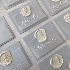Provence inspired wedding day place setting tags with white calligraphy names on vellum with blue grey card and a white olive branch wax seal