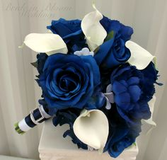 """A wedding bouquet of class and elegance. The real touch calla lilies are soft to touch and look so real, you are sure to love them. Bouquet is designed with 10 creamy white calla lilies, royal blue hydrangea, white stephanotis, with blue roses. Handle treatment is wrapped with a white satin ribbon, navy blue & black satin sash, finished with a sparkling rhinestone buckle. Bouquet measures 10"""" ( 25 cm ) wide x 12"""" ( 30 cm ) tall."""